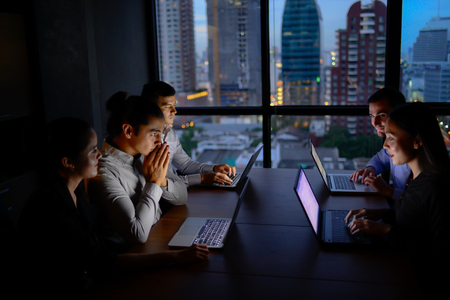 business team working with computer overtime at night and low light Stock Photo