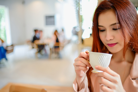 Portrait of beautiful woman and holding a cup of coffee in her hand in blur background coffee shop, she drink coffee in the morning Stock Photo