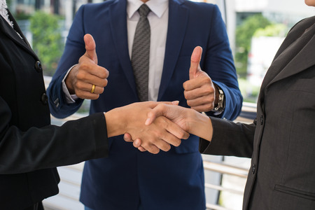 business man show thumb up and two business woman shaking hands for demonstrating their agreement to sign agreement or contract between their firms, companies, enterprises. success concept Stock Photo