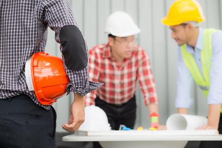 安全ヘルメットを着用し、テーブルの上に青写真を見て、エンジニアと建設チーム。工事現場の進捗状況の確認に取り組んでいる。エンジニアリングおよびクライアントが材料をレビューし、建設現場エリアの建設プロセスを確認します。
