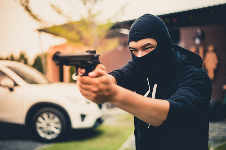 Picture of Criminal or Bandit wear black mask useing gun point to somewhere, concept of criminal, bandit, gangster, mafia Stock Photo