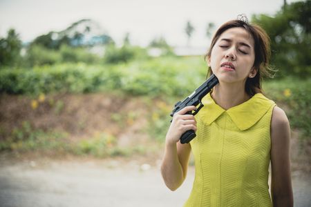 Stressed woman with holding gun on her chin point to her head.She is saddened by the disappointment in love. concept of broken heart, heartbroken, lovelorn, Suicide. Stock Photo