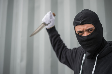 portrait of criminal or bandit wear black mask holding a knife and looking to camera, concept of cutthroat and assassin Archivio Fotografico