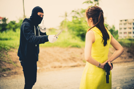 Criminal or Bandit wear black mask use knife point to woman trying to rob money and hurting her but the woman but women hid their guns behin, concept of winner, fighting, usurpation
