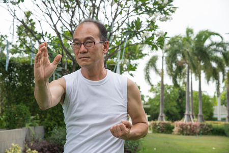 asian senior man wear white shirt stand and practice tai chi on the grass in the park