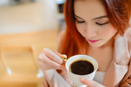 Portrait of beautiful face woman and holding a cup of coffee in her hand in blur background coffee shop, she drink coffee in the morning Stock Photo