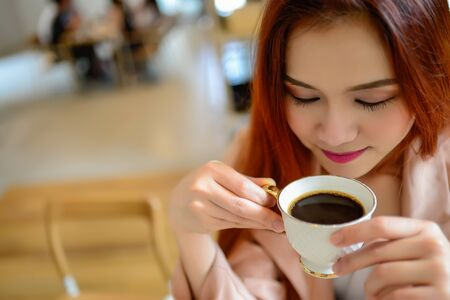 Portrait of beautiful face woman and hand holding a cup of coffee in her hand in blur background coffee shop, she drink coffee in the morning Stock Photo