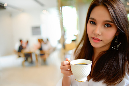 Portrait of beautiful woman holding a cup of coffee in her hand in blur background coffee shop, she drink coffee in the morning Stock Photo