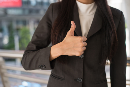 close up hand of business woman showing thumb up in the city, business success concept