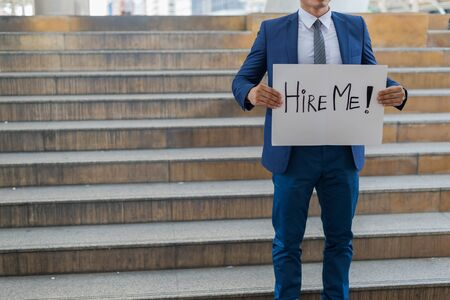 Hire me! Handsome businessman wear blue suit holding poster with hire me text message while standing outdoors and against building structure 写真素材