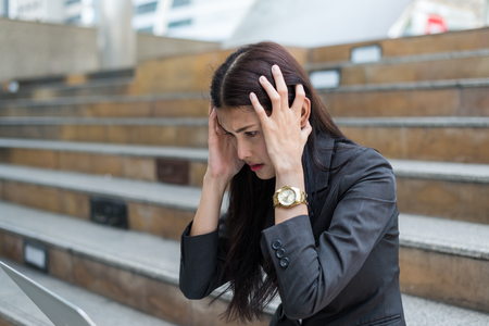 A businesswoman sit on the stairs and her hands clasped head,the feeling of stressed, sadness or displeasure caused by the non fulfillment of one's hopes or expectations. Banque d'images