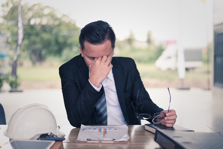 businessman sitting and his hand clasped head, he is feeling of stressed and sadness, concept of business failure and financial problem. Reklamní fotografie
