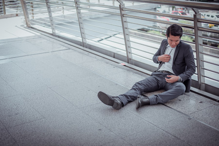 businessman unemployed from company sitting on street, he is feeling of stressed and sadness, concept of business failure and unemployment problem.