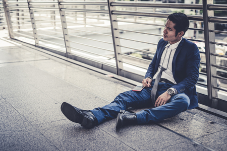 businessman unemployed from company sitting on street, he is feeling of stressed and sadness, concept of business failure and unemployment problem. vintage style