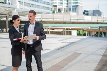 Asian businesswoman and Caucasian businessman discussion business issue from financial report on paper, they are standing in the city and buildings background.