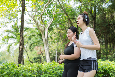 blurred motion of fat woman and thin woman exercise by jogging in the park, they are running for health and lose weight. Stock Photo