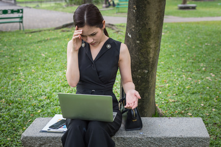 businesswoman sit in the garden and her hand clasped head, the feeling of stressed, sadness or displeasure caused by business failure.