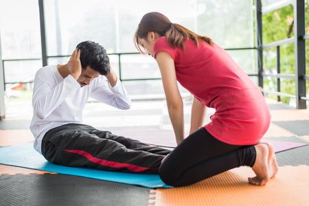 woman trainer help sportsman sit ups in gym