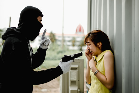 Criminal or Bandit wear black mask and black clothes using gun point to woman for rob money and hurting her.