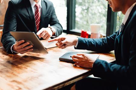 twee zakenman zitten en kijken naar tablet, ze ontmoeten elkaar over businessplan, marketing en financieel in de toekomst. concept van zakelijk succes, zakelijke bijeenkomst.