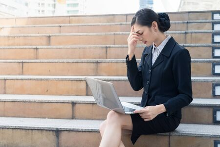 Asian businesswoman sit on the staircase and looking at laptop. she stress and used her hand to touch her head.