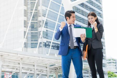 Asian businessman and businesswoman standing in the city and raise hand up to celebrate for business success. with copy space for text Stock Photo