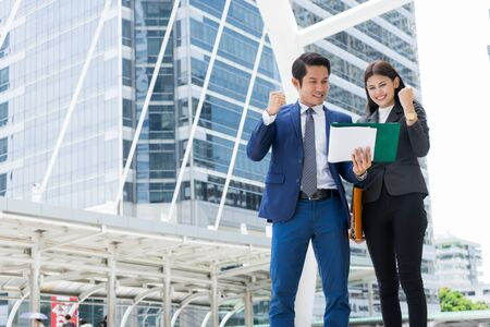 Asian businessman and businesswoman holding document and rising up hand. concept of business success.