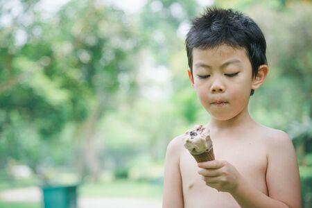 garçon mangeant un cornet de crème glacée dans le jardin