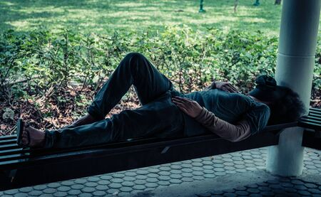 Poor homeless man or refugee sleeping on a seat in the park. social documentary concept.