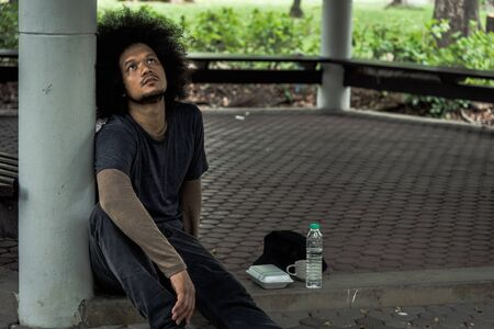 Poor homeless man or refugee sit on a the floor in the park. social documentary concept.