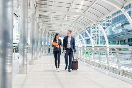 businessman with luggage and businesswoman with document file on hand walk together in the city, business travel concept