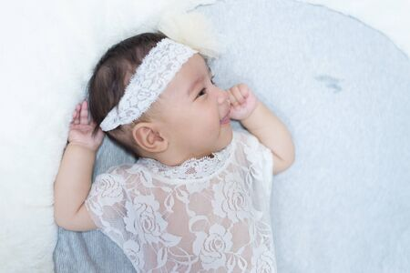 little baby with white ctrue dress poses for a photo shoot.