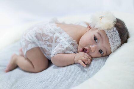 adorable little baby with white ctrue dress poses for a photo shoot.