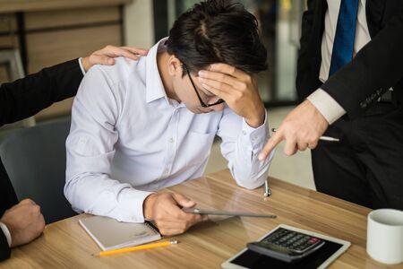 homme d'affaires a crié à l'employé et a pointé son doigt pour signaler, il est très en colère pour la baisse des ventes signalée. l'employé est stressé et met les mains sur sa tête.