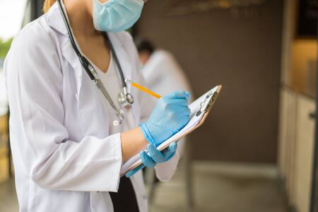 image of woman doctor in white coat with stethoscope and blue glove write report by pencil in a notebook on blur background of hospital.