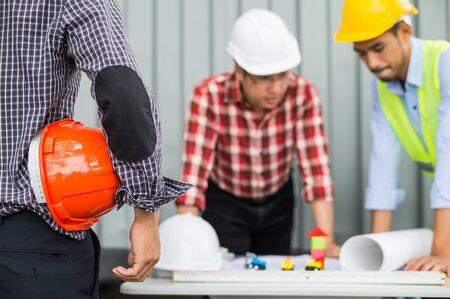 ingeniero y equipo de construcción con casco de seguridad y trabajando verificando el progreso de la construcción en el plano, revisando el material y verificando el proceso de construcción en el área del sitio de construcción.