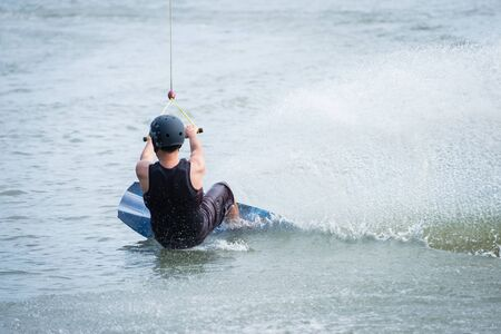 A man playing wakeboard to fast and water splash at the lake. water sport at extreme park Stock Photo