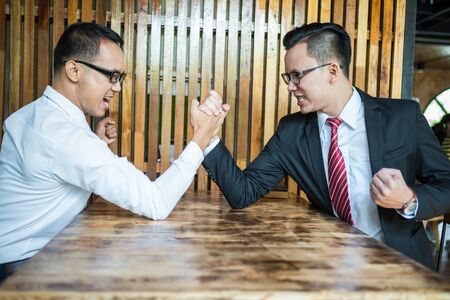 Two businessman expressed a serious expression and fighting by used arm wrestling on wood table. concept of business competition