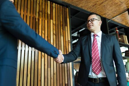 two businessman shaking hands for demonstrating their agreement to sign contract between company. concept of success, dealing, greeting and partner concept.