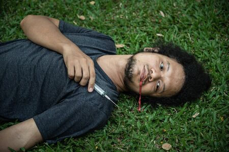 drug addict dead on the grass and bleed from the mouth after injecting too much. Concept of drug addiction and overdose.