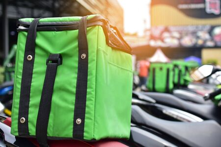 The green bag on the motorcycle of the food delivery staff waits to put food in order to deliver to customers from online food ordering. Archivio Fotografico