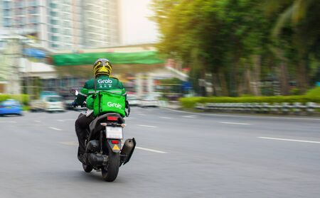 Motorcycle driver urgently delivers food to customers who order online in Bangkok, Thailand, 28-04-2020.