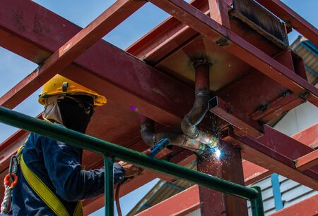 The welder stands on a steel roof structure at the building construction area. Skilled worker is connecting with high steel structure in construction project Foto de archivo