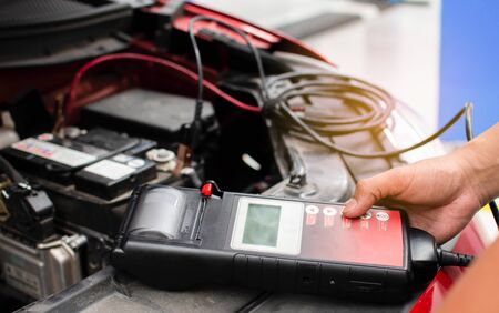 The mechanic uses the equipment to check the voltage of the car batteries in the service center and the motor vehicle repair center.