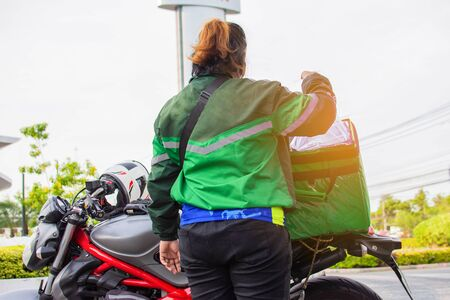The female staff prepares food in the bag on the motorcycle to deliver the food to the customers ordered online.