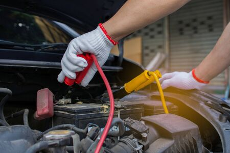 The hands of technicians use charging cables for batteries for cars. The concept of attaching batteries to start a broken car.