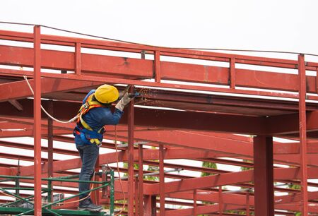 Large steel structures are connected to create a building with skilled steel technicians.
