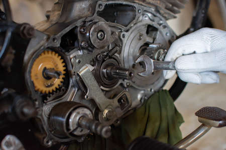 Mechanic uses a motorcycle engine repair machine Banco de Imagens