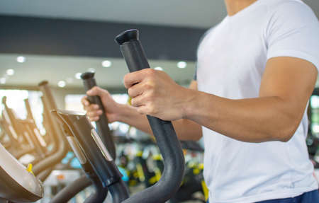 Men use arm and leg exercise machines at the fitness center in the morning. Zdjęcie Seryjne