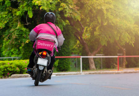 The delivery staff of the pink form uniform is driving the motorcycle to deliver the products to customers who order online.